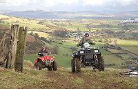 Two All Terrain Vehicles climbing a hill in Wales,