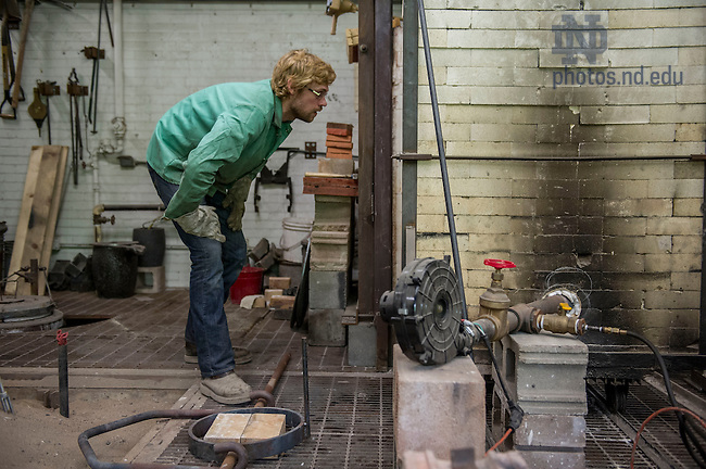 July 17, 2014; Benjamin Sunderlin works on the bell casting process in his foundry in Riley Hall.  (Photo by Barbara Johnston/University of Notre Dame