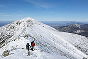 Two hikers traveling south on the Appalachian Trail (Franconia Ridge Trail) in the White Mountains, New Hampshire during the winter months.