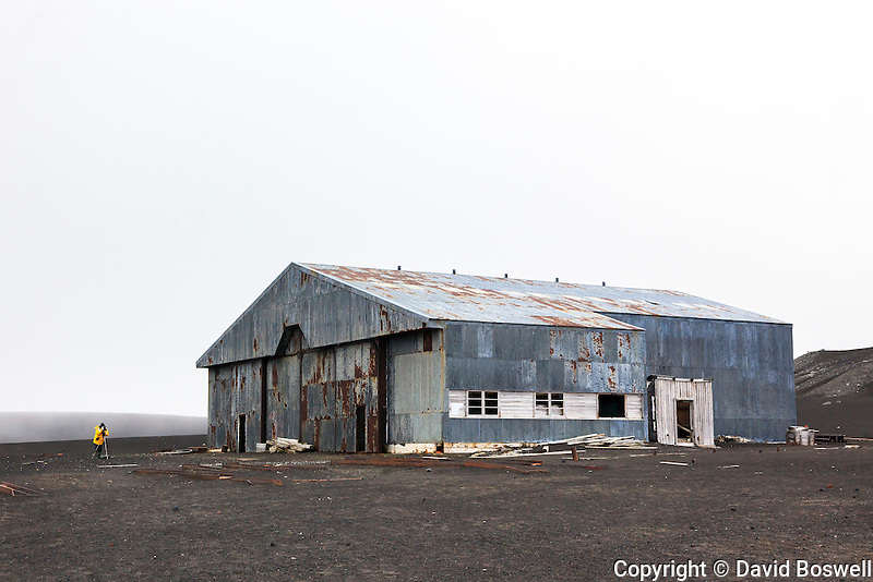 A photographer at a decrepit British hanger at Whalers Bay on Deception Island, in the South Shetland Islands near the Antarctic Peninsula.  Whalers Bay is the site of a Norwegian whaling base operating from 1911-1931 when it was abandoned due to the decline of the whaling industry.  In 1944 the British used the building for a base they operated here until 1969 when they too abandoned the base, this time due to volcanic activity.