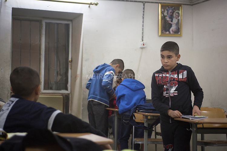 15/11/14. Alqosh, Iraq. Wassam (right) speaks to a another orphan during a session of studying and drawing held at a classroom in the orphanage during the evening.