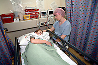 Nurse monitoring a child in the paediatric recovery room of a hospital operating theatre after the child under went an operation. The nurse will remain with the child until she has recovered from the anaesthetic. This image may only be used to portray the subject in a positive manner..©shoutpictures.com..john@shoutpictures.com