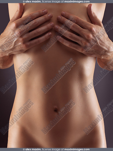 Sensual nude couple closeup photo of mans hands covering naked woman breasts