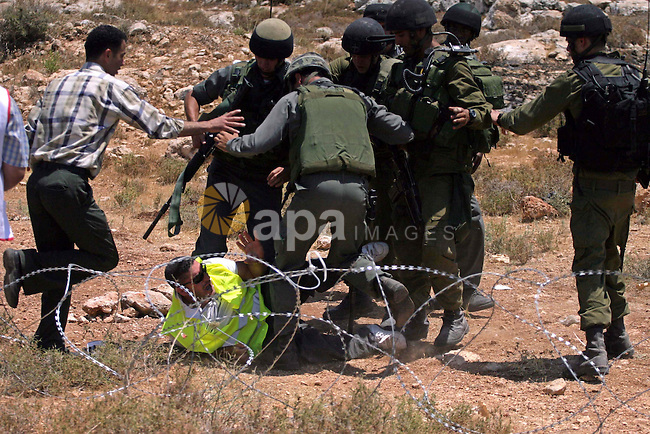 Palestinians scuffle with Israeli border police officers during a demonstration against Israel's controversial separation barrier in the West Bank village of Nilin, near Ramallah. Five Palestinians were wounded today as Israeli soldiers fired rubber bullets at demonstrators protesting at the construction of a separation wall on the outskirts of Nilin, medics said.