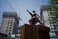 A statue of Chinese woman singer Li yuchun is seen in front of a construction site of residential blocks in Songzhuang Artist Village of Beijing on May 31, 2012. The village is the most famous and biggest artist community in Beijing with about 5,000 artists living there. (Leica M9, 28mm f2)