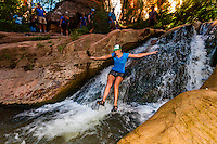 People sliding down a small waterfall on the Kanarra Creek Falls hike near Cedar City, Utah USA.