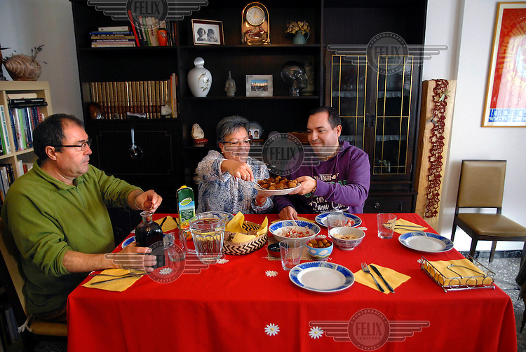 A portrait of Alejandro Cao de Benos, photographed in the village of Salomo in northeast Spain having a meal with his parents Rafael and Elvira. As a Korean-Spanish communist, Alejandro is the president of the Korean Friendship Association (KFA) and has been an advocate of the Democratic People's Republic of Korea (North Korea) since 1990. His Korean name is Zo Sun-il (Korea is One) and he works as an honorary Special Delegate of the DPRK's Committee for Cultural Relations with Foreign Countries - a North Korean government spokesman in Europe.