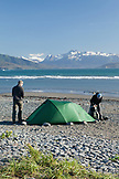 ALASKA, Homer, travelers set up camp at the end of the Homer Spit, Land's End, with the Kenai Mountains in the background, Kachemak Bay