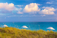 Three umbrellas and three clouds. Grace Bay, Providenciales. Turks and Caicos.