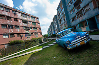 "A classic American car is seen parked in front of the apartment block in Bahía, a public housing suburb of Havana, Cuba, 11 February 2011. The Cuban economic transformation (after the revolution in 1959) has changed the housing status in Cuba from a consumer commodity into a social right. In 1970s, to overcome the serious housing shortage, the Cuban state took over the Soviet Union concept of social housing. Using prefabricated panel factories, donated to Cuba by Soviets, huge public housing complexes have risen in the outskirts of Cuban towns. Although these mass housing settlements provided habitation to many families, they often lack infrastructure, culture, shops, services and well-maintained public spaces. Many local residents have no feeling of belonging and inspite of living on a tropical island, they claim to be ""living in Siberia""."