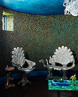 A custom-made peacock feather wall-covering adorns the library, with 18th century grotto chairs placed around a malachite table