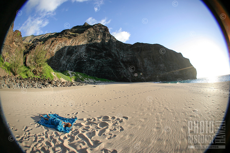 A young woman sleeps on a blue cloth at Honopu Beach, Na Pali Coast, Kaua'i.