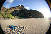 A young woman sleeps on a blue cloth at Honopu Beach, Na Pali Coast, Kaua'i.