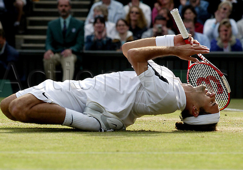 4 July 2004: Swiss defending champion ROGER FEDERER (SUI) falls to his knees in celebration at the moment he clinches his second men's singles title with victory over Roddick in the men's singles Final at the All England Lawn Tennis Championships, Wimbledon, London. Federer beat Roddick 4-6, 7-5, 7-6, 6-4 Photo: Leo Mason/Action Plus...040704 Tennis man joy celebrate celebrates celebrations winner winners