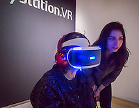 A worker assists a visitor to Sony Square in New York on Monday, February 27, 2017 as she tries out the Sony Playstation VR virtual reality headset. The headset, an add-on to existing Playstation 4 consoles, has been very popular due to the existing market of Playstation owners. (© Richard B. Levine)
