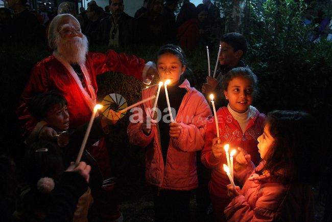 Palestinian children hold candles as they stand near a large lit Christmas tree in the West Bank city of Ramallah, Monday, Dec. 20, 2010. Photo by Issam Rimawi