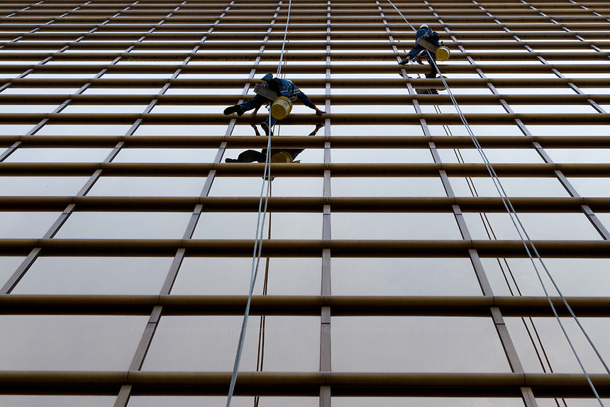 Window cleaners using ropes to abseil off a building in Yokohama, Kanagawa, Japan. Friday May 3rd 2019