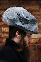 A Jewish covers his hat from the rain in Union City, NJ, during a day of 4 inches of snow and almost 1/2 of ice which made this Wednesday a hard commute for people around New York and New Jersey. Jan 05, 2014. Photo by Eduardo Munoz Alvarez/VIEWpress