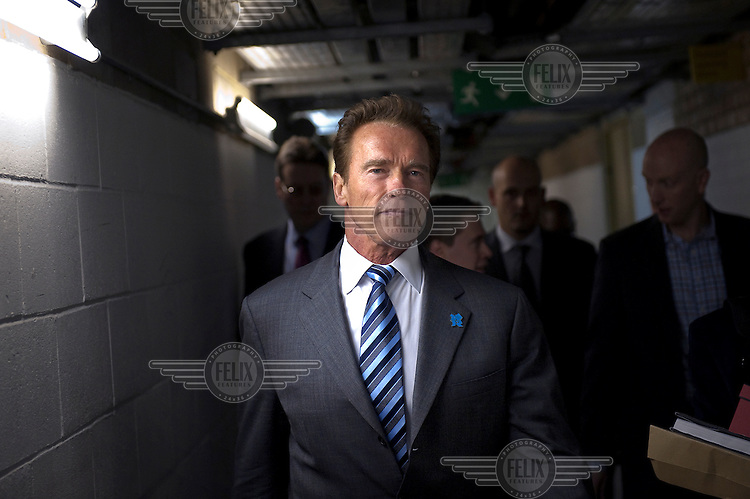 Arnold Schwarzenegger leaves City Hall in London through a basement corridor.