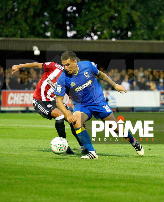 AFC Wimbledon's Cody McDonald turns his marker during the Carabao Cup match between AFC Wimbledon and Brentford at the Cherry Red Records Stadium, Kingston, England on 8 August 2017. Photo by Carlton Myrie.