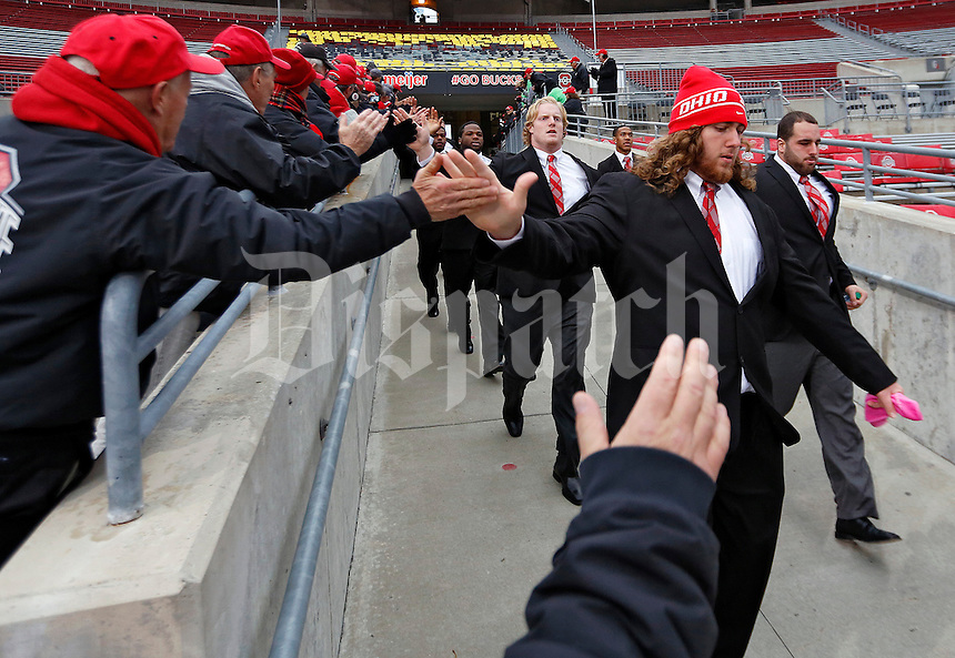 Ohio State Buckeyes offensive linesman Andrew Norwell (78) high-fives ushers as the team walks into the stadium before their game against Penn State Nittany Lions at Ohio Stadium on October 26, 2013.  (Dispatch photo by Kyle Robertson)