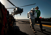 101208-N-7981E-808 PACIFIC OCEAN (Dec. 8, 2010)- Lt. J.G. Dennis Pelina and Ship's Serviceman 3rd Class Tyriek Lyons run to clear the danger area after attaching cargo to the underside of an SH-60B Seahawk on the flight deck of the aircraft carrier USS Carl Vinson (CVN 70) during a vertical replenishment at sea with the fleet replenishment oiler USNS Yukon (T-AO 202). Carl Vinson and Carrier Air Wing (CVW) 17 are currently on a three-week composite training unit exercise (COMPTUEX) followed by a western Pacific deployment. (U.S. Navy photo by Mass Communication Specialist 2nd Class James R. Evans / RELEASED)