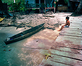 PANAMA, Bocas del Toro, Salt Creek Islands, Guaymi Indian boy sits on a dock by a dugout canoe, Central America