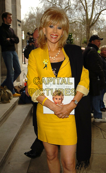 SALLY FARMILOE.At the Memorial Lunch and unveiling of a plaque in memory of Sir John Mills, Grosvenor House, London, England, April 9th 2006..half length yellow suit skirt jacket holding sensual pleasures book charity wrist band bracelet daffodil.Ref: CAN.www.capitalpictures.com.sales@capitalpictures.com.©Can Nguyen/Capital Pictures..