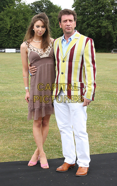 GUEST & NICK KNOWLES .Duke Of Essex Polo Trophy at Gaynes Park, Epping, Essex, England, UK,.July 4th 2009..full length brown dress yellow and red striped suit jacket blazer white trousers shoes .CAP/ROS.©Steve Ross/Capital Pictures