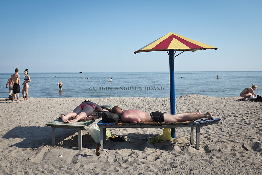 UKRAINE, Mariupol: A couple is sunbathing at Orjonikija beach in eastern part of Mariupol. At only 10km away, the frontline of Sherokyne...