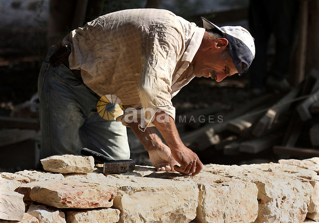 A Palestinian worker builds a wall in West Bank city of Jericho , on Oct. 11.2010 . Jericho is one of the oldest continuously inhabited cities in the world, with evidence of settlement dating back to 9000 BC,it has a population of over 20,000 Palestinians. Situated well below sea level on an east-west route 16 kilometres (10 mi) north of the Dead Sea, Jericho is the lowest permanently inhabited site on earth . Photo by Eyad Jadallah