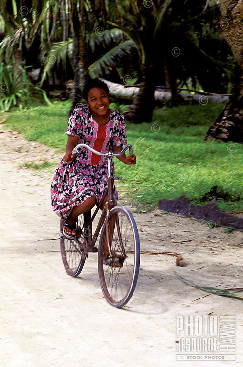 Smiling girl rides bicycle down palm lined road in Yap, Micronesia.