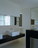 The use of mirrors in this sleek contemporary bathroom gives the room an increased sense of space and light