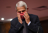 Dr. Anthony Fauci, director of the National Institute for Allergy and Infectious Diseases, adjusts his face mask as he prepares to testify before the Senate Health, Education, Labor and Pensions (HELP) Committee on Capitol Hill in Washington DC on Tuesday, June 30, 2020.  Fauci and other government health officials updated the Senate on how to safely get back to school and the workplace during the COVID-19 pandemic.<br /> Credit: Kevin Dietsch / Pool via CNP /MediaPunch