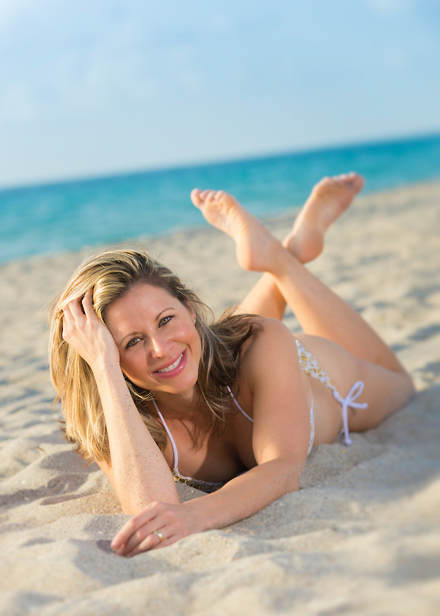 Young woman very happy lying on the sand in the beach.