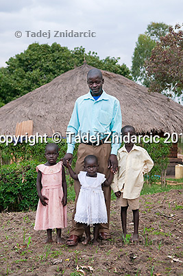 Valente Inziku with his children (L to R) Patricia Alezuyo, Convert Diana, and Joshua Tabu in front of their home in Aribio village, Arua district, Uganda. Valente Inziko's wife Jennifer Anguko bled to death during childbirth in October 2010 in Arua Hospital. Jennifer Anguko was a local councilor and the death of her and the baby was widely reported.