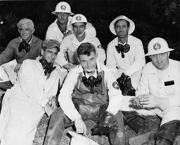 Time out from grim work for these workers, 7 of the 12 members of the Civil Defense Body Hunt Detail. From left to right first row, are: Frank Dunn, Richard Thompson, and Mason Goldman. Second row, from left to right, are: George Guy, John Gudonis, Peter Pocius, and James Simpson.