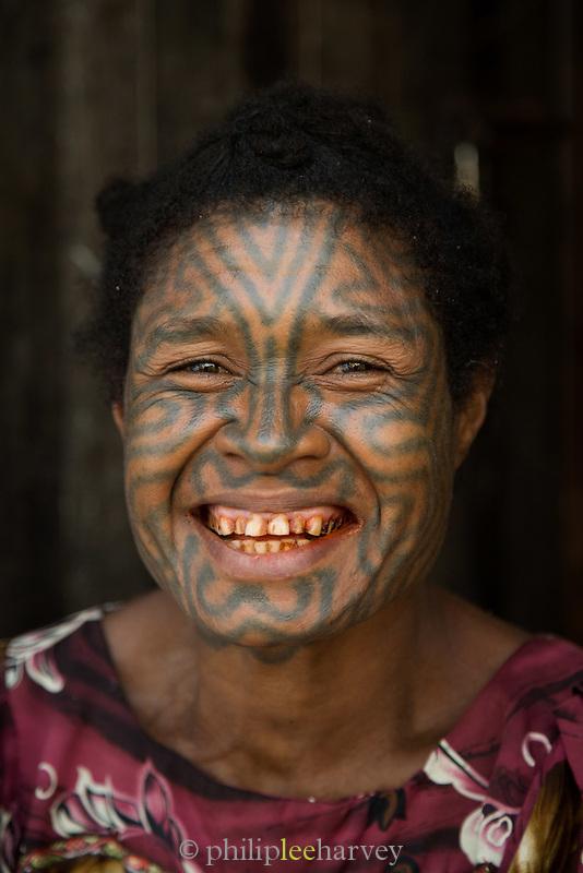 woman with traditional facial tattoos at Tufi market, Tufi, Cape Nelson, Oro Province, Papua New Guinea