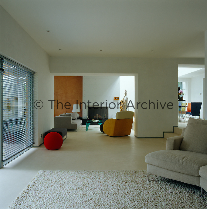 A large expanse of polished limestone floor, punctuated by a round red cushion, separates the home cinema from the main living area