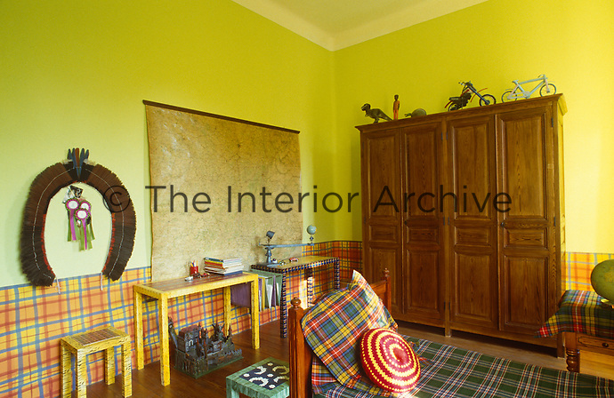 A boy's bedroom has been decorated in playful fashion with plaid used for bed cover, cushions, tablecloth and even painted around the walls