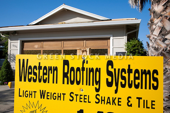 Western Roofing Systems sign spelling 'Western Roofing Systems - Light Weight Steel Shake & Tile' in front of a residential house with a roof being refurbished.
