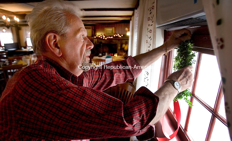 WOODBURY CT. 02 December 2014-120214SV01-Robert Steponaitis puts a wreath on a window of the Curtis House Inn while decorating for the holidays in Woodbury Tuesday. The Curtis House will host a wine tasting fundraiser on Dec. 12 from 5-7:30pm. The event is sponsored by the Woman&rsquo;s Club of Woodbury.<br /> Steven Valenti Republican-American