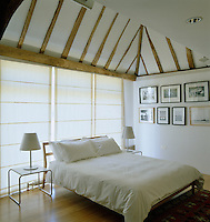 A simple bedroom has floor-to-ceiling blinds that diffuse the light coming in through the glass wall