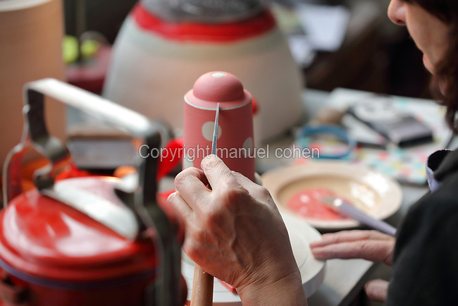 Ceramicist Valeria Polsinelli decorating a vase on a turntable with coloured glazes, photographed in 2017, in her studio in Montreuil, a suburb of Paris, France. Polsinelli creates everyday vessels, water jugs, jewellery and figurines and stoppers of female busts, with features and hairstyles from various world cultures. Picture by Manuel Cohen