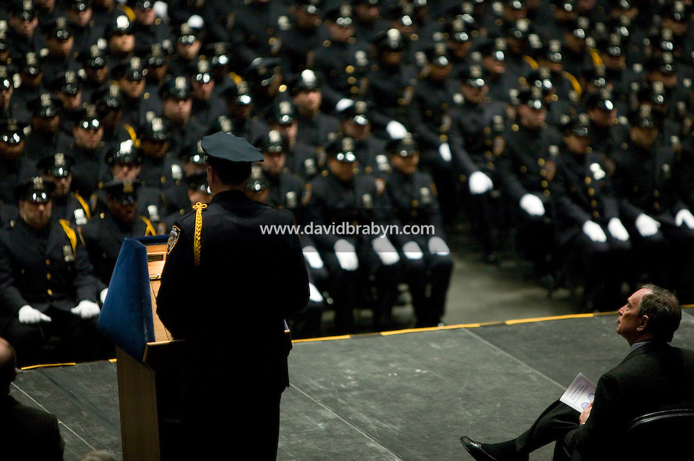 29 December 2005 - New York City, NY - New York City Mayor, Michael Bloomberg (R, foreground) listen to Police Officer Charles M. Mills deliver the valedictoriam address to the New York Police Department's Class of 2005 during their graduation ceremony, 29 December 2005, at the Madison Square Garden in New York City. 1,735 recruits were sworn in during the ceremony.
