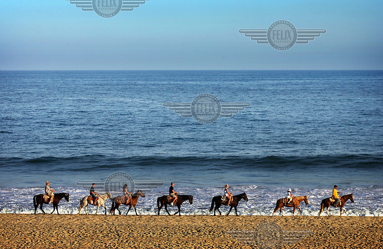 Tourists enjoy riding horses along the beach in the small city of Cabo San Lucas on the Southern tip of the Baja California peninsula.