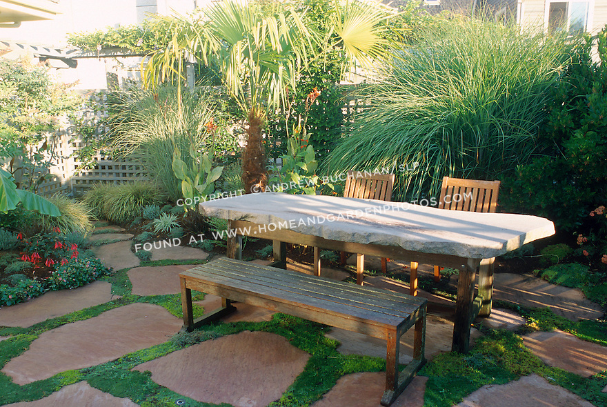 A stone slab picnic table is one of the unique elements in this lush tropical yard.