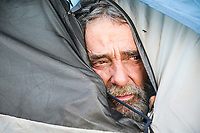 James Royce Jordan looks out his tent under the Houston Harte Expressway in San Angelo.