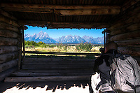 Andrew Tan photographing the Grand Tetons through the dilapidated Cunningham Cabin built in 1885