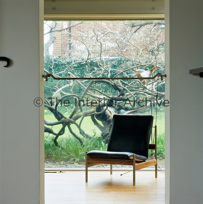A retro chair is silhouetted against a floor-to-ceiling glass window with views onto the garden